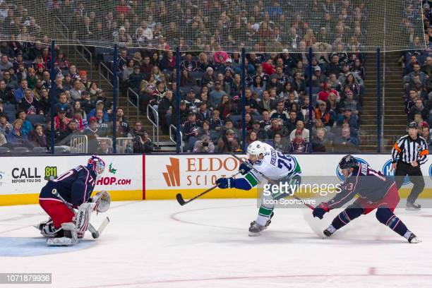 Vancouver Canucks left wing Antoine Roussel attempts a shot as Columbus Blue Jackets goaltender Joonas Korpisalo defends in a game between the...