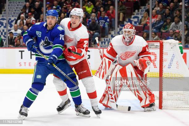 Vancouver Canucks Left Wing Tanner Pearson and Detroit Red Wings Defenceman Dennis Cholowski stand in front of Goalie Jonathan Bernier during their...
