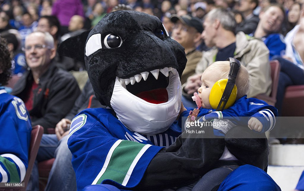 Vancouver Canucks mascot Fin holds Emmanuella Dykes during the third period in NHL action on March 19, 2013 at Rogers Arena in Vancouver, British Columbia, Canada.