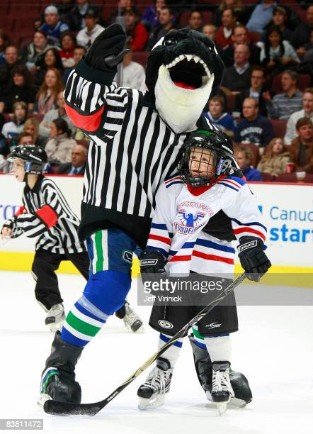 Vancouver Canucks mascot Fin hugs defenceman Sami Salo's son Oliver Salo at General Motors Place on November 24 2008 in Vancouver British Columbia...