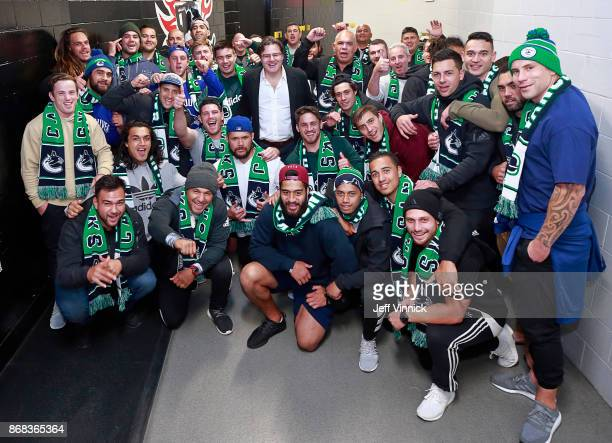 Vancouver Canucks owner Francesco Aquilini poses with The Maori All Blacks rugby team before the NHL game between the Vancouver Canucks and the...