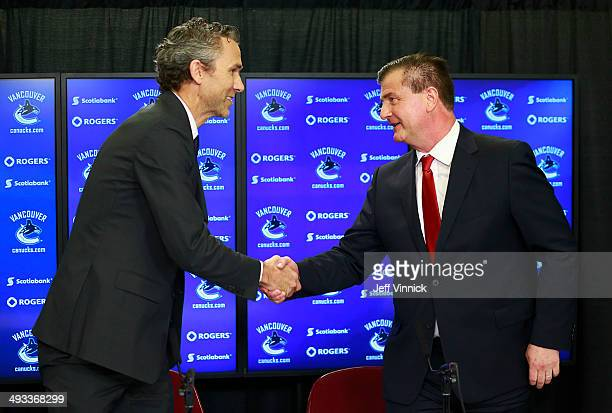 Vancouver Canucks President Trevor Linden shakes hands with Jim Benning as he introduces him as the team's new General Manager during a press...