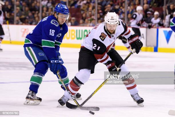 Vancouver Canucks Right Wing Jake Virtanen and Arizona Coyotes Center Derek Stepan battle for the puck during their NHL game at Rogers Arena on March...