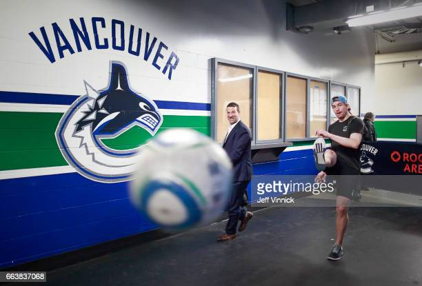 Vancouver Canucks skills coach Glenn Carnegie looks on as Sven Baertschi of the Vancouver Canucks kicks a soccer ball before their NHL game against...