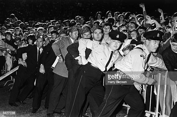 Vancouver Police and security guards hold back Beatles fans at a concert in Vancouver during the group's North American tour
