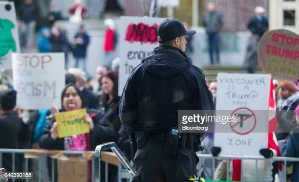 A Vancouver Police Department officer stands guard as protesters demonstrate outside the Trump International Hotel Tower during the opening ceremony...