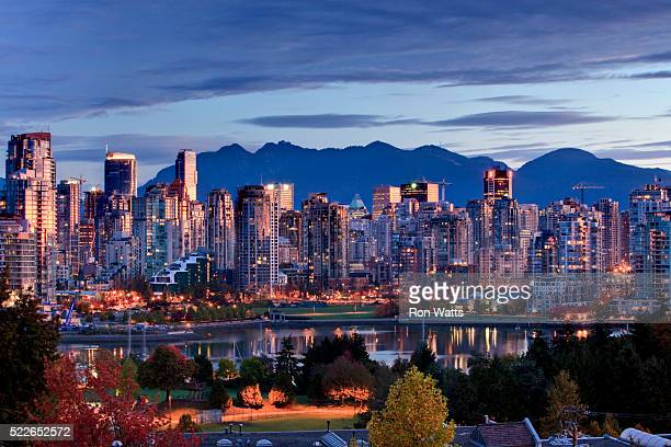 vancouver skyline in front of north shore mountains - vancouver stock-fotos und bilder