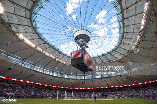 Vancouver Whitecaps and Seattle Sounders stand on the field under an open roof during the national anthems prior to their match at BC Place on August...