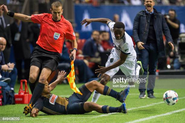 Vancouver Whitecaps forward Alphonso Davies and Philadelphia Union defender Fabinho fall into the assistant referee during the game between the...