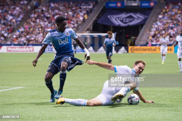 Vancouver Whitecaps forward Alphonso Davies and Seattle Sounders defender Chad Marshall battle for the ball during their match at BC Place on August...