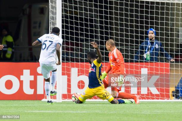 Vancouver Whitecaps forward Alphonso Davies scores a goal on New York Red Bulls goalkeeper Luis Robles during the CONCACAF Champions League...