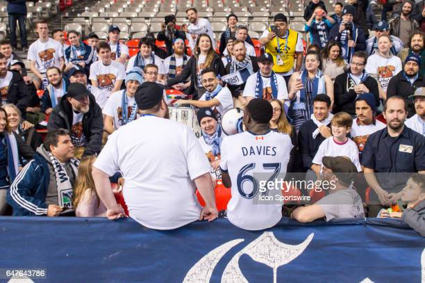 Vancouver Whitecaps forward Alphonso Davies sits with fans after the CONCACAF Champions League Quarterfinal game between the Vancouver Whitecaps and...