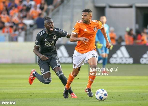 Vancouver Whitecaps forward Kei Kamara trips as Houston Dynamo defender Leonardo takes the ball during the soccer match between the Vancouver...