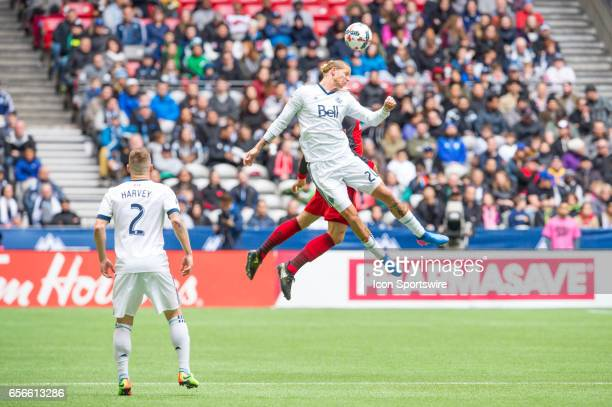 Vancouver Whitecaps midfielder Brek Shea jumps to head the ball as Vancouver Whitecaps defender Jordan Harvey looks on during their match against...
