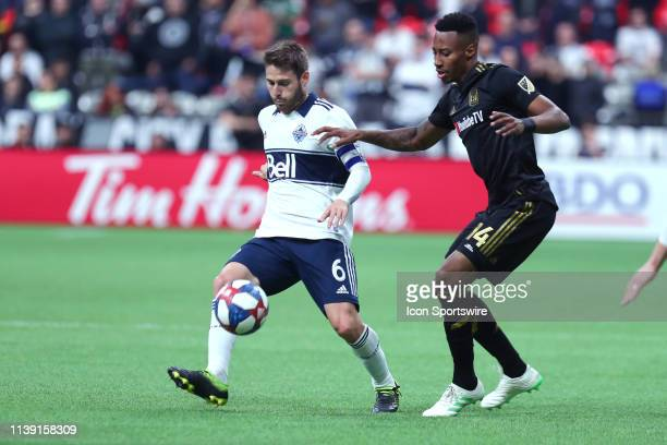 Vancouver Whitecaps midfielder Jon Erice runs with the ball and avoids a check from Los Angeles FC midfielder MarkAnthony Kaye during their match at...