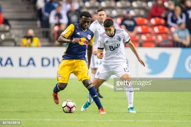 Vancouver Whitecaps midfielder Matias Laba defends against New York Red Bulls midfielder Derrick Etienne during the CONCACAF Champions League...