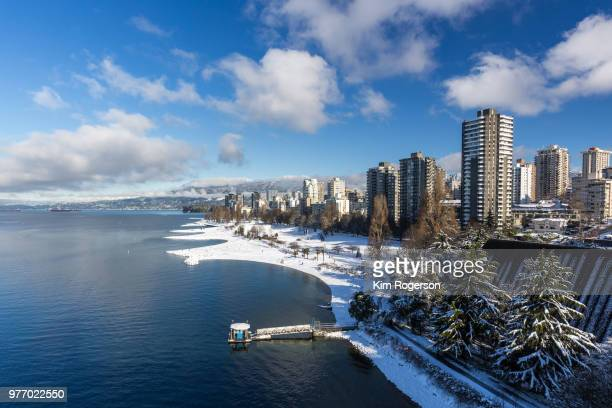 vancouver's english bay & residential area with winter snowfall - english bay stock photos and pictures