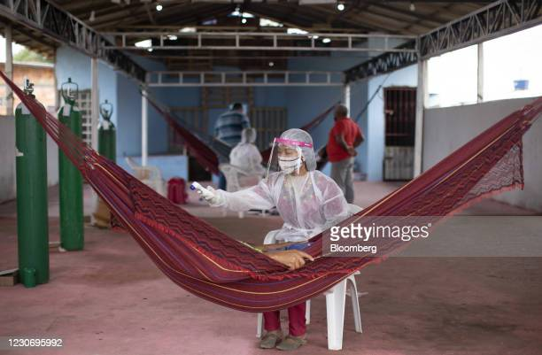 Vanda Ortega, a nurse and member of the Witoto indigenous tribe, takes the temperature of a Covid-19 patient at the Indian campaign hospital set up...