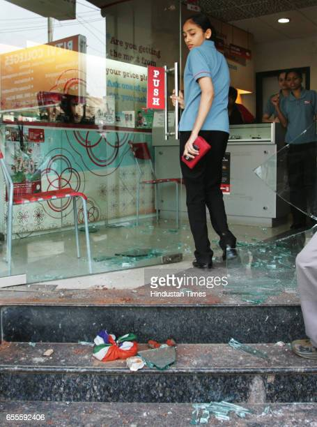 Vandalisation Violence Employee of Airtel store at Bandra looks at the shattered glass of the store and the stone that was thrown by unidentified...