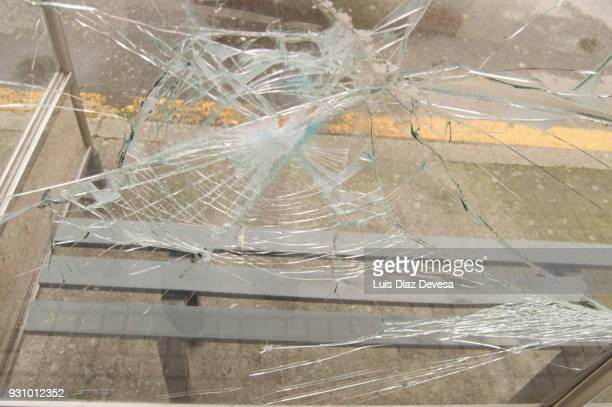 vandalised and smashed window in a bus shelter