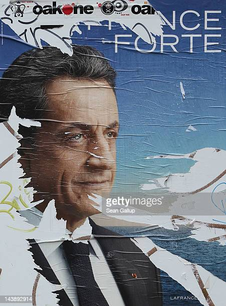 A vandalised election poster showing French President Nicolas Sarkozy hangs on a wall in a street the day before the second round of French...