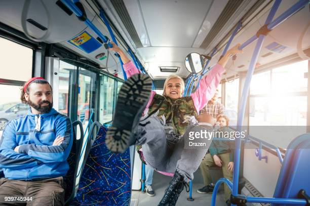 Vandalism in the public bus - woman kicking passengers