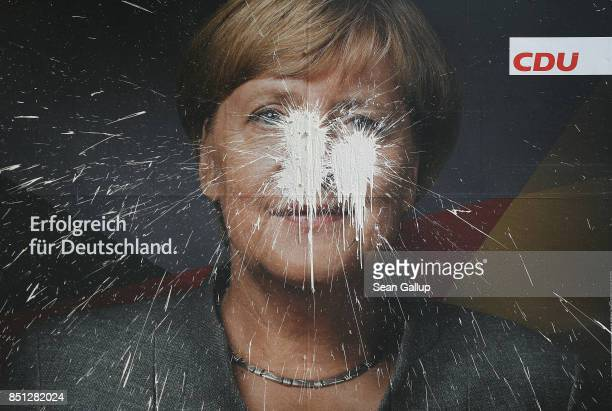 A vandalized election campaign billboard that shows German Chancellor and Christian Democrat Angela Merkel and reads 'Successful for Germany' stands...