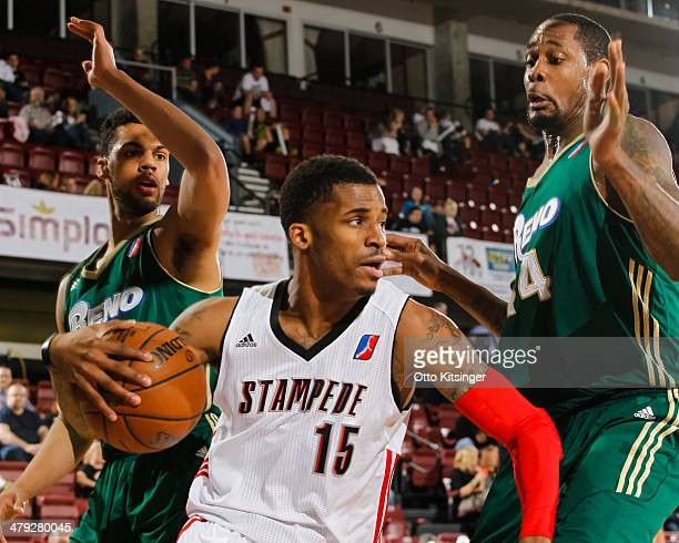 Vander Blue of the Idaho Stampede moves the ball around Trent Lockett and Mickell Gladness of the Reno Bighorns during an NBA D-League game on March...