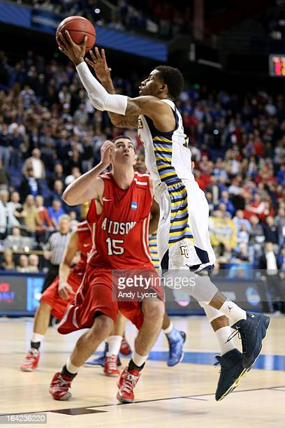 Vander Blue of the Marquette Golden Eagles scores the game-winning basket against Jake Cohen of the Davidson Wildcats to put Marquette ahead 59-58...