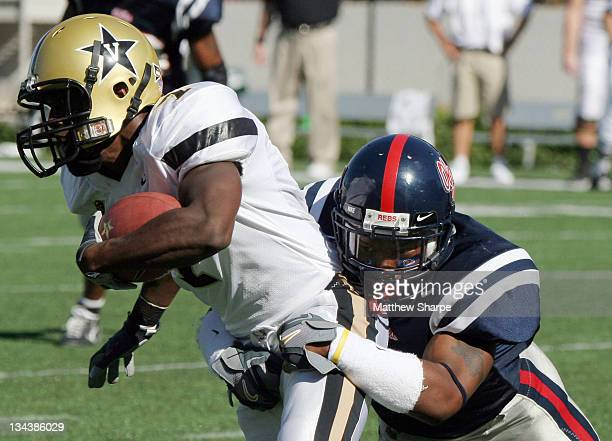 Vanderbilt wide receiver Sean Walker moves up the field being dragged by Ole Miss defensive back Bryan Brown at VaughtHemingway Stadium in Oxford...