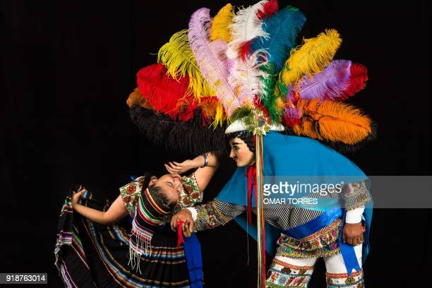 Vanesa Calderon and Vladimir Mejia pose in their costumes for the carnival of Tlaxcala Mexico on February 13 2018 The satirical costumes and masks...