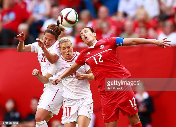 Vanessa Bernauer and Lara Dickenmann of Switzerland and Christine Sinclair of Canada head the ball during the FIFA Women's World Cup Canada 2015...