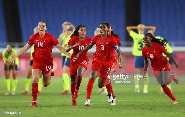 Vanessa Gilles, Ashley Lawrence and Kadeisha Buchanan of Team Canada celebrate following their team's victory in the penalty shoot out in the Women's...