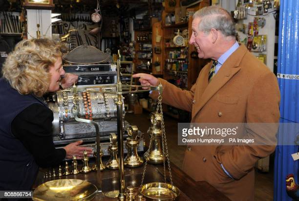 Vanessa Graham from the J.B Banks & Son ltd ironmongers, one of the oldest shops in Cockermouth, shows Prince Charles the old till they still use.