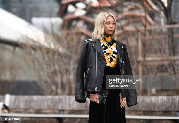 Vanessa Hong is seen wearing a black leather jacket and yellow and black painted sweater outside the Proenza Schouler show during New York Fashion...