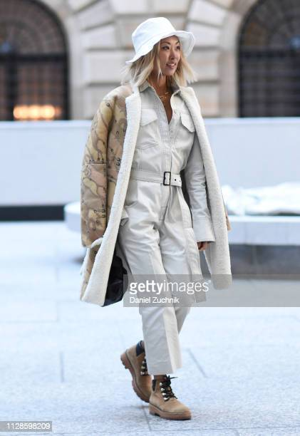Vanessa Hong is seen wearing a white hat, white one piece, black bag and brown shoes outside the Longchamp show during New York Fashion Week:...