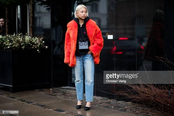 Vanessa Hong wearing belt bag red coat black hoodie denim jeans outside Anne Vest during the Copenhagen Fashion Week Autumn/Winter 18 on January 31...