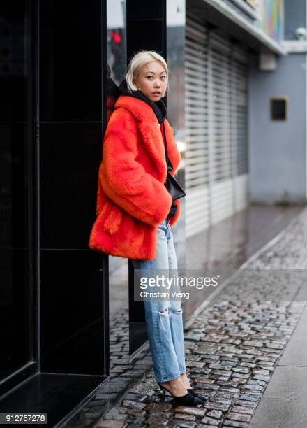 Vanessa Hong wearing belt bag red coat black hoodie denim jeans outside Anne Vest during the Copenhagen Fashion Week Autumn/Winter 18 on January 31...