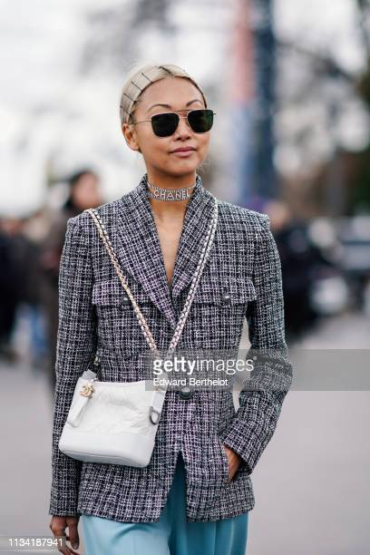 Vanessa Hong wears a gray checked blazer jacket, a white Chanel bag, sunglasses, a Chanel choker, hair brooches, outside Chanel, during Paris Fashion...