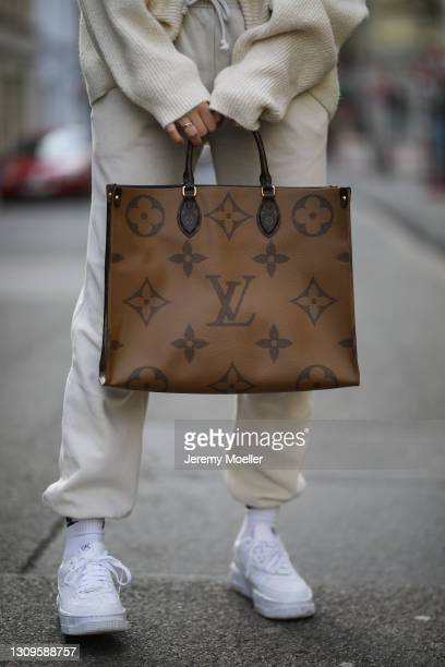Vanessa Stanat wearing beige Zara sweater, Louis Vuitton On The Go brown monogram travel bag, beige Nike sweatpants, white Nike socks and Nike Air...