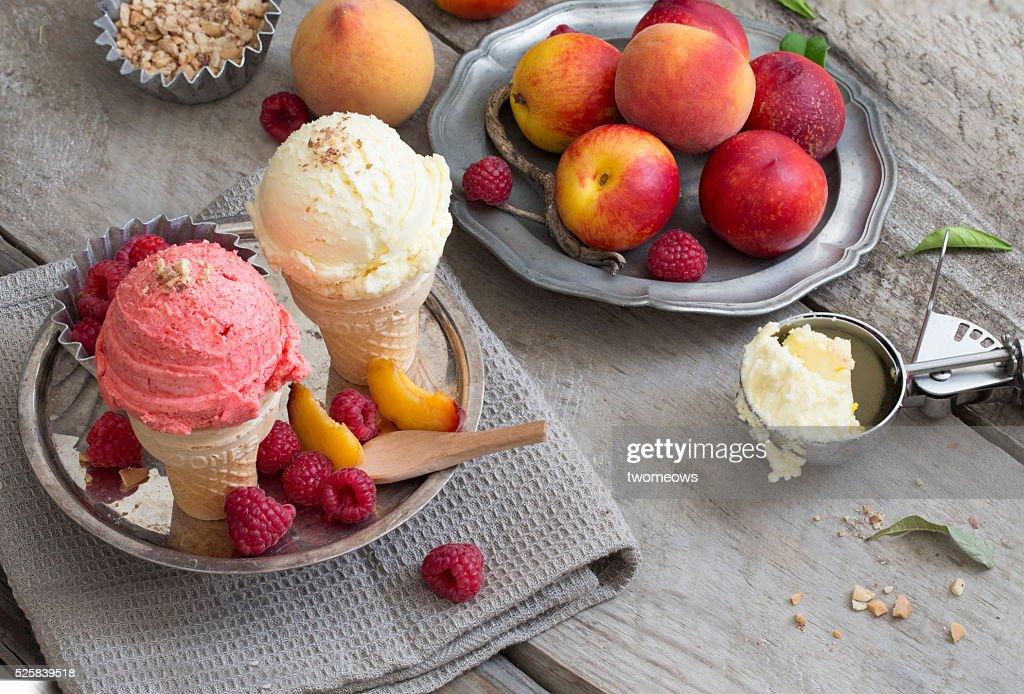 Vanilla and strawberry ice cream ball on cone. Rustic wooden background. : Stock-Foto