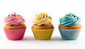 Vanilla cupcakes with pink yellow and blue icing isolated