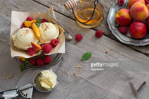 Vanilla ice cream balls with fresh berries and mint leaf served with strawberry syrup on moody rustic wooden table top.
