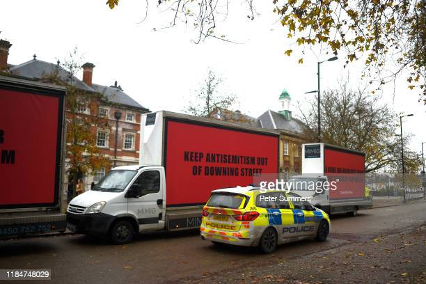 Vans belonging to The Community United against Labour Party antiSemitism group Culpa are parked next to a police car ahead of the Labour Race and...