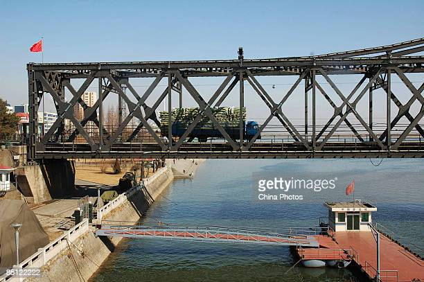 Vans ride across the Sino-Korean Friendship Bridge on February 26, 2009 in Dandong of Liaoning Province, China. The Yalu River, now a tourist...