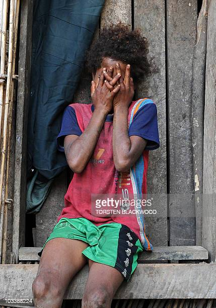 STORY 'VanuatuBritainreligionroyalsFEATURE' by Madeleine Coorey A Tannese girl waits outside the chef's hut to catch a glimpse of Britain's Prince...