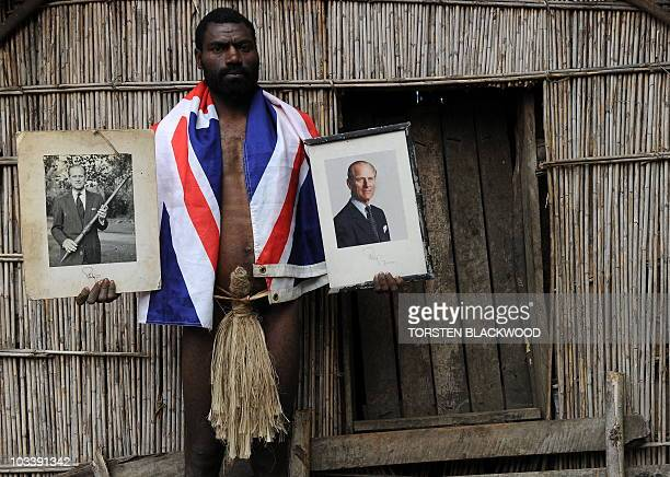 STORY 'VanuatuBritainreligionroyalsFEATURE' by Madeleine Coorey Sikor Natuan the son of the local chief holds two official portraits of Britain's...