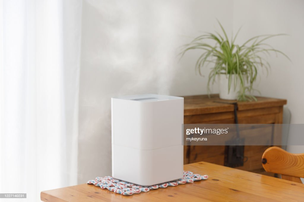 Vapor from humidifier in front of window.Disinfecting of room to prevent COVID-19 : Stock Photo