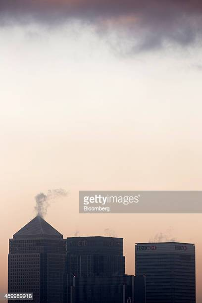Vapor rises from the tops of One Canada Square, left, Citigroup Inc., center, and HSBC Holdings Plc, at dawn in the Canary Wharf business, financial...