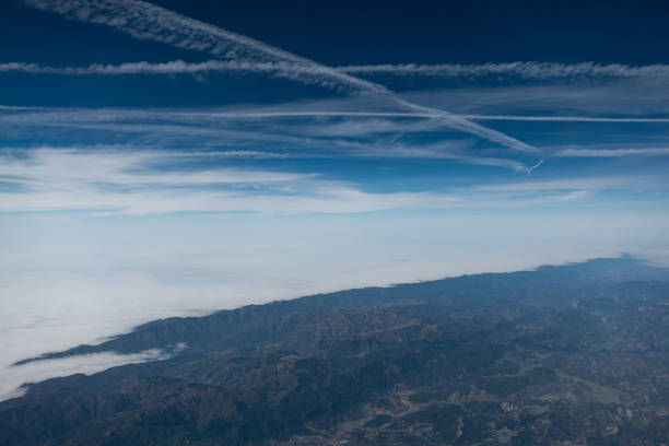 Vapor trail in the sky of California, daytime aerial view from airplane